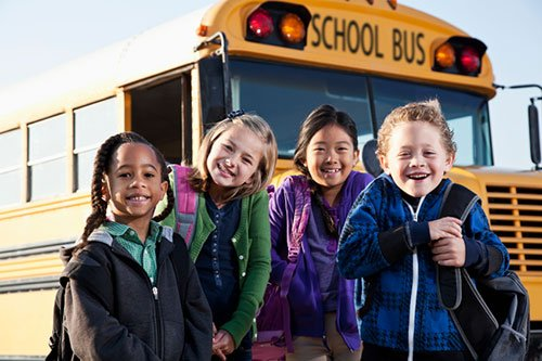 Group of smiling kids standing by the school bus