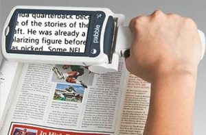 A person using a magnifier to read the newspaper as an example of tools to assist those who are visually impaired