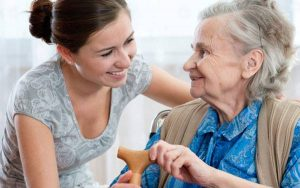 A smiling lady leans over to talk and help and older woman in a chair