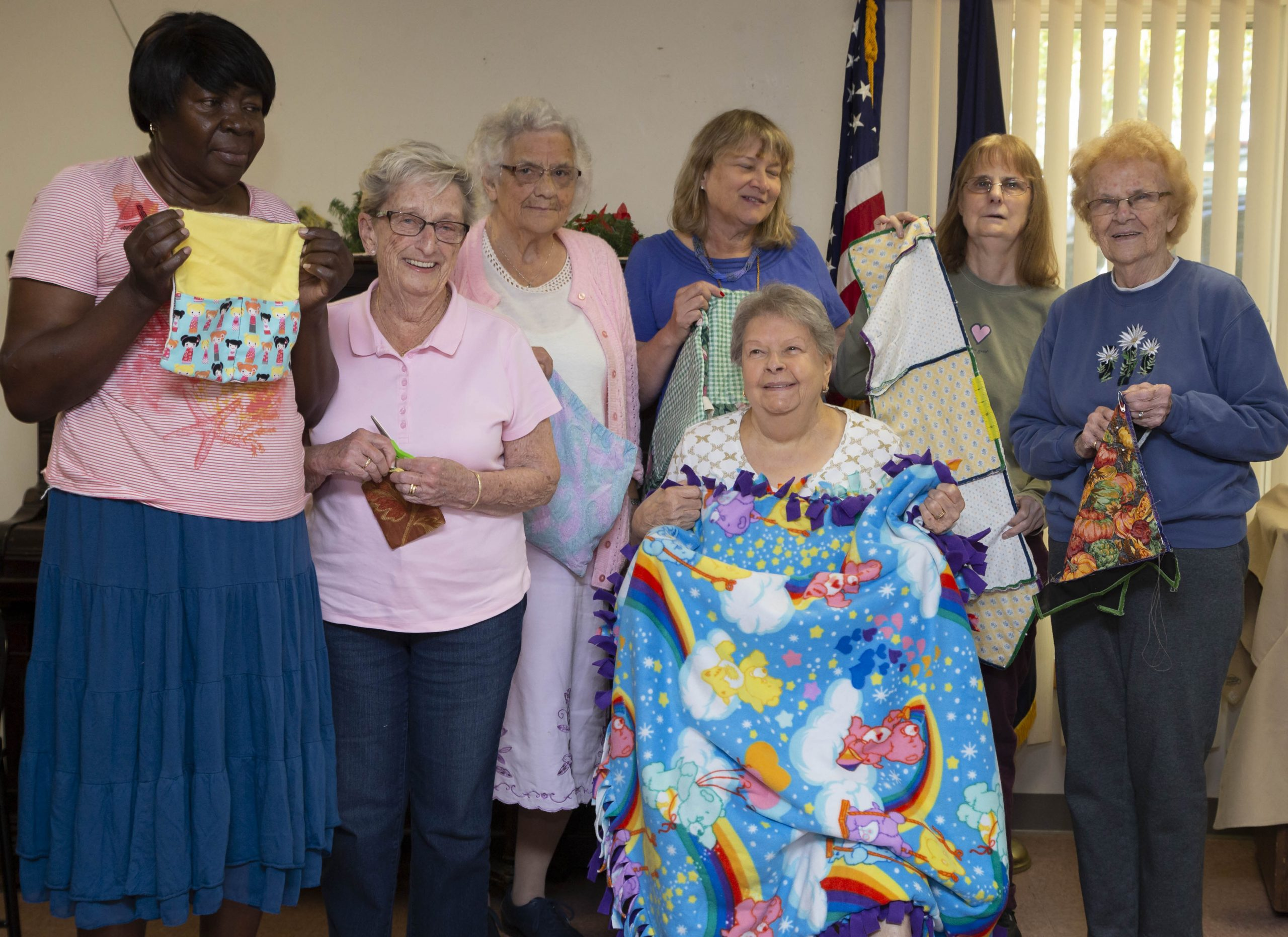 The adaptive sewing group proudly displays their work