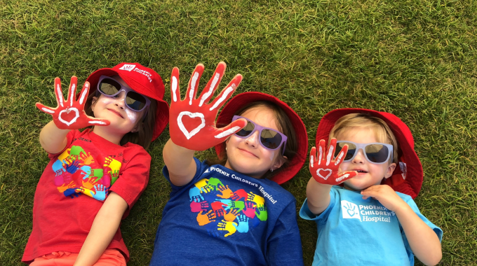 Three Kids laying in the grass having fun with hearts painted on their hands