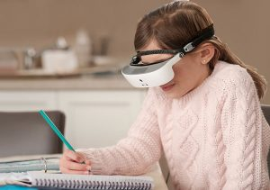 Girl with goggle reading and writing