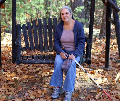 Linda Armijo sitting on a wooden swinging bench surrounded by fall leaves.