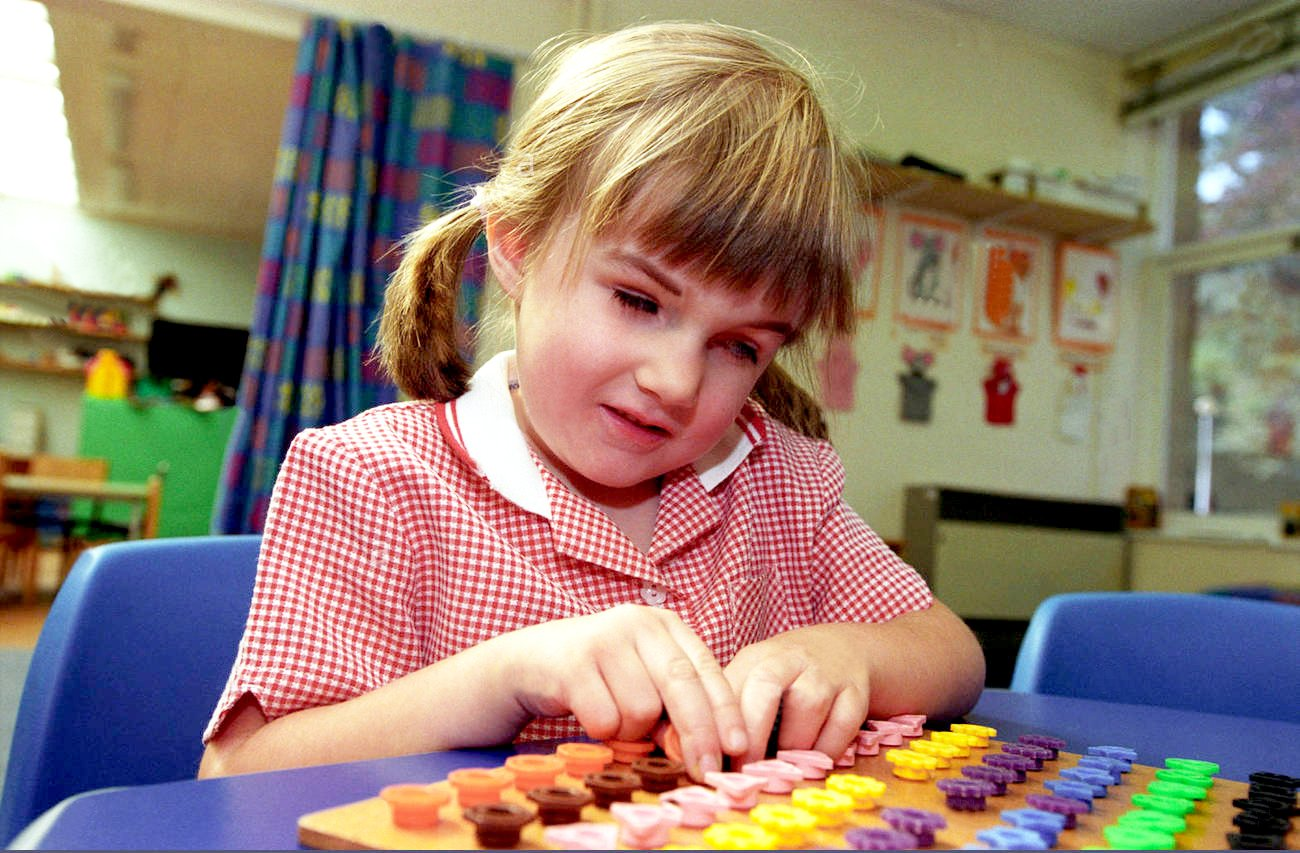 A young girl in pigtails and a red checkered dress plays with a colorful board game.