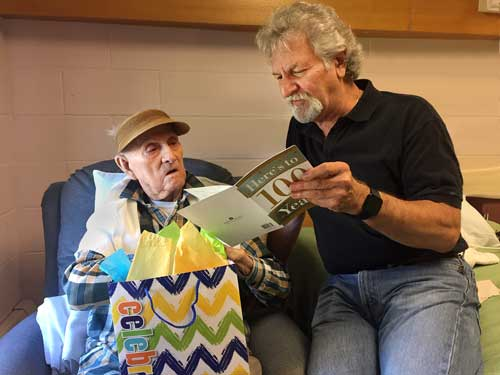 A volunteer reading birthday cards to a client on his 100th birthday
