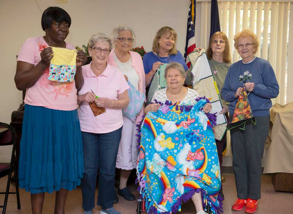 The Manchester Mitsy Kits Adaptive Sewing Group poses together for a group shot while holding their current projects. From left to right: Joyce Fearon, Barbara Dickson, Therese Goodno, Joan Pinard (seated), Diane McClung behind her, Cheryl Thomas and Leona Thomas.