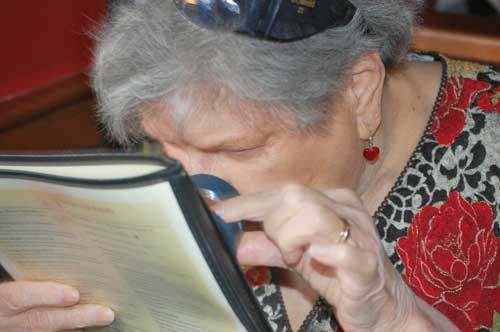 Joan Pinard using a magnifier to read
