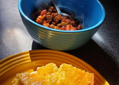 Sun shining on a closeup of cornbread and chili on the table
