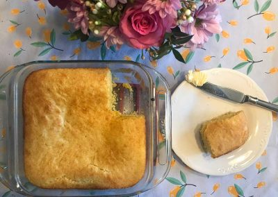 Perfect setting, slice of cornbread ready to butter - Pink flowers in a vase and a floral tablecloth