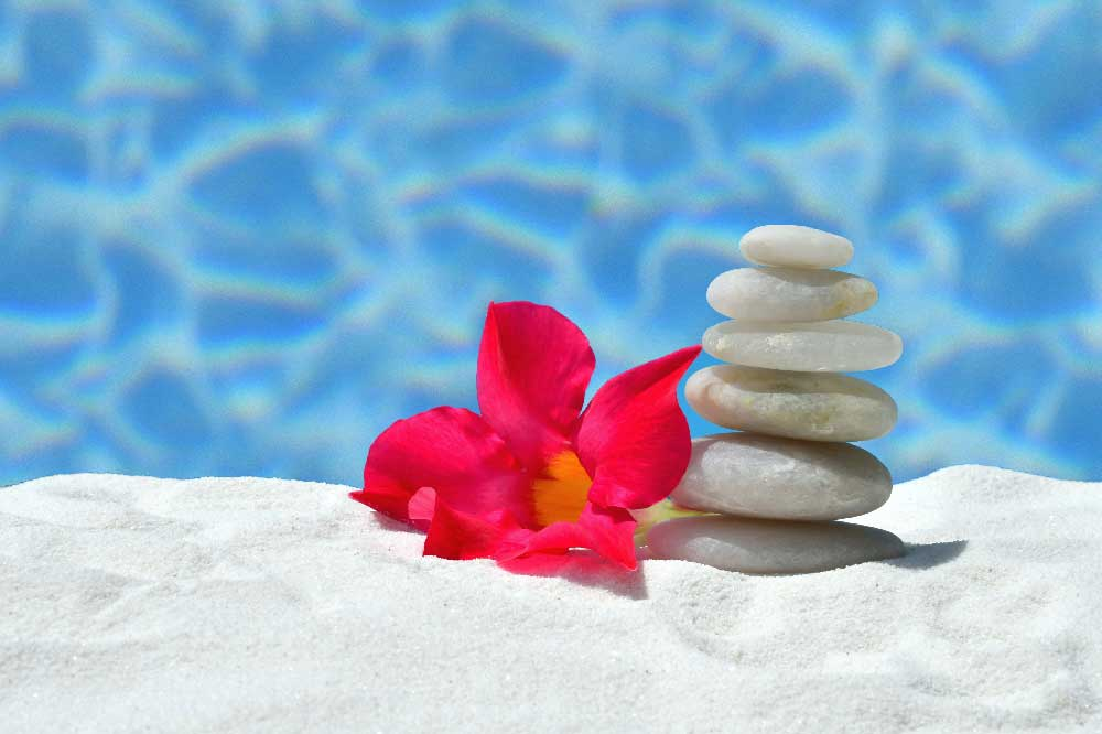 Balanced white rocks stacked in white beach sand with a bright pink flower