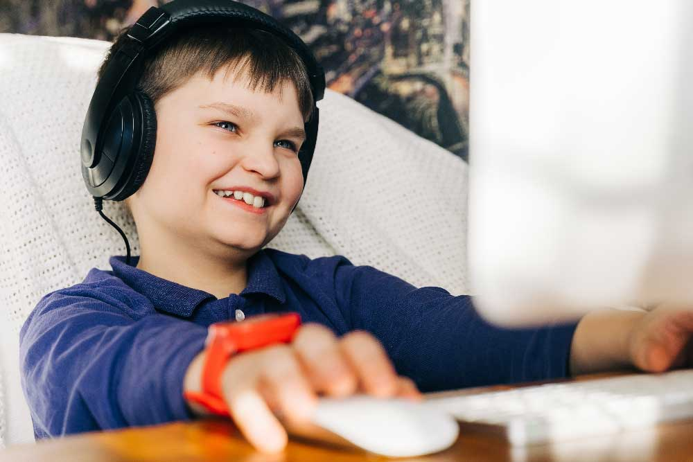 A young boy smiling with headphones on playing a game with friends on the computer